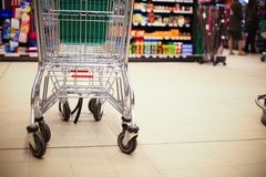 Shopping cart in supermarket. Empty shopping cart in big store with products and few people in background. Shop concept Royalty Free Stock Images