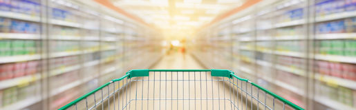 Shopping cart with supermarket aisle blur background Royalty Free Stock Images