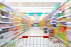 Shopping cart with supermarket aisle blur background. Shopping cart with supermarket aisle blur abstract background royalty free stock photo
