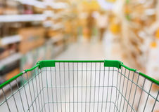 Shopping cart with Supermarket Aisle with product on Shelves Stock Photos