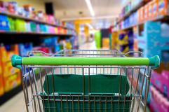Shopping cart in the supermarket aisle rear view Royalty Free Stock Images