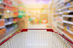 Shopping cart in Supermarket Aisle and Shelves in blur backgroun Stock Image