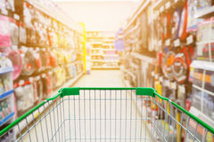 Shopping cart with Supermarket Aisle and Shelves Royalty Free Stock Photo