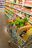 Shopping cart in a supermarket. A shopping cart is a aisle of a supermarket in the stacks Stock Images