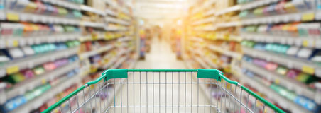 Shopping cart with supermarket for background. Shopping cart with supermarket in blurry for background, panorama view royalty free stock image