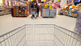 Shopping cart in supermarket, blurred background Royalty Free Stock Photos