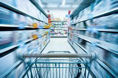 Shopping cart and supermarket. Empty shopping cart and abstract blurred supermarket background Royalty Free Stock Image