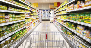 Shopping cart in the supermarket. An empty shopping cart between rows of shelves in the supermarket Royalty Free Stock Photo