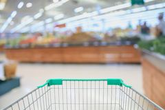 Shopping cart with Supermarket with fresh food. Abstract blurred background with bokeh light Royalty Free Stock Image