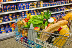 Shopping cart in a supermarket. A shopping cart is a transition between the shelves of a supermarket Royalty Free Stock Images