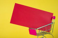 Shopping cart or supermarket trolley and blank red envelop on ye. Llow background with space for add text, Chinese new year and shopping concept idea Stock Photography