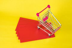 Shopping cart or supermarket trolley and blank red envelop on ye. Llow background with space for add text, Chinese new year and shopping concept idea Royalty Free Stock Photo