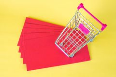 Shopping cart or supermarket trolley and blank red envelop on ye. Llow background with space for add text, Chinese new year and shopping concept idea Royalty Free Stock Photography