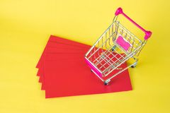 Shopping cart or supermarket trolley and blank red envelop on ye. Llow background with space for add text, Chinese new year and shopping concept idea Royalty Free Stock Photos