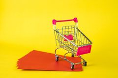 Shopping cart or supermarket trolley and blank red envelop on ye. Llow background with space for add text, Chinese new year and shopping concept idea Royalty Free Stock Image
