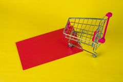 Shopping cart or supermarket trolley and blank red envelop on ye. Llow background with space for add text, Chinese new year and shopping concept idea Stock Images
