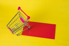 Shopping cart or supermarket trolley and blank red envelop on ye. Llow background with space for add text, Chinese new year and shopping concept idea Royalty Free Stock Images