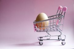 Shopping cart. Supermarket trolley with egg on pink background. Consumerism concept photo. Shopping cart. Supermarket trolley full with big Egg on pink Royalty Free Stock Photos