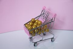Shopping cart. Supermarket trolley full of golden balls on pink background. Consumerism concept photo. Shopping cart. Supermarket trolley full of golden balls Stock Image