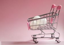 Shopping cart. Supermarket trolley full of white balls on pink background. Consumerism concept photo. Shopping cart. Supermarket trolley full of white balls on Stock Image