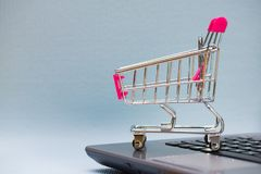 Shopping cart or supermarket trolley with laptop notebook on grey background, e-commerce and online shopping concept. Shopping cart or supermarket trolley with stock photos