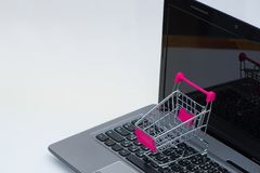 Shopping cart or supermarket trolley with laptop notebook on white background, e-commerce and online shopping concept. Shopping cart or supermarket trolley with stock images