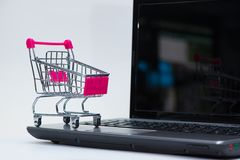 Shopping cart or supermarket trolley with laptop notebook on white background, e-commerce and online shopping concept. Shopping cart or supermarket trolley with stock photo