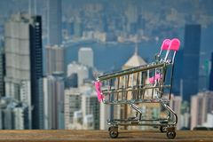 Shopping cart or supermarket trolley on top wooden working table. With city and office building background, business and financial concept idea Royalty Free Stock Photography