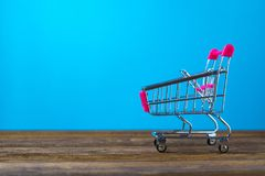 Shopping cart or supermarket trolley on wooden table with copy s. Pace for business finance shopping and marketing concept Stock Images