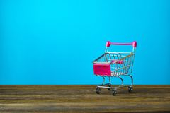 Shopping cart or supermarket trolley on wooden table with copy s. Pace for business finance shopping and marketing concept Stock Photography