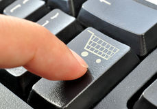 Shopping cart symbol. Finger pressing down on an enter key with a shopping cart icon Royalty Free Stock Photos