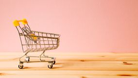 Shopping cart on table. Shopping cart on wooden table Stock Photo