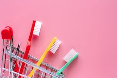 Shopping cart with toothbrush on pink background. For market and dental care concept stock photography
