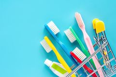 Shopping cart with toothbrush and toothpaste on blue background. For market and dental care concept stock photography