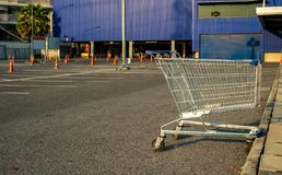 Shopping cart with traffic cone in store parking lot,blue background.  stock images