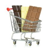 A shopping cart trolley with bars of chocolate. On a white background Royalty Free Stock Photos