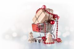 Shopping cart or trolley with Christmas gift boxes, red  ornamen Stock Photography