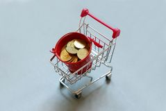 Shopping cart or trolley fill with red pile of coins on grey background.Business and finance concept. Shopping cart or trolley fill with red pile of coins on stock images