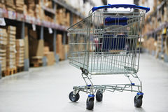 Shopping cart trolley in warehouse. Shopping trolley cart before Rows of shelves with storage boxes in huge warehouse Royalty Free Stock Images