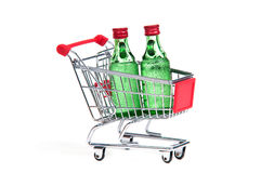 Shopping cart with two glass bottles Stock Photos