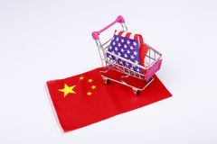 Shopping cart with USA flag on China flag Stock Photos