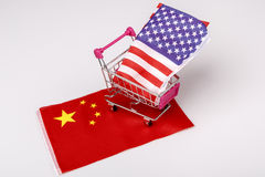 Shopping cart with USA flag on China flag Royalty Free Stock Photo