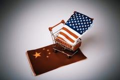 Shopping cart with USA flag on China flag Stock Photography