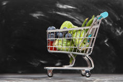Shopping cart with vegetables. On black background Royalty Free Stock Photos