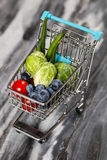 Shopping cart with vegetables. On black background Royalty Free Stock Image