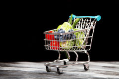 Shopping cart with vegetables on black background.  Stock Images