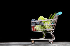 Shopping cart with vegetables on black background.  Stock Image