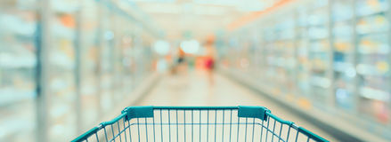 Shopping cart view in supermarket aisle with refrigerators. Blurred background, vintage tone Stock Photos
