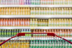 Shopping cart view in Supermarket with beverage product Shelves. In blurry for background royalty free stock photos