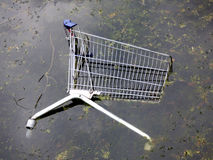 Shopping cart in the water. Shopping cart thrown in the water Stock Photo